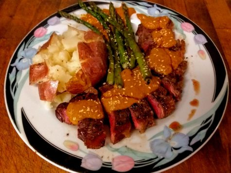 Medium-rare grilled New York strip steak with mole, asparagus and baked potato, topped with toasted sesame seed.