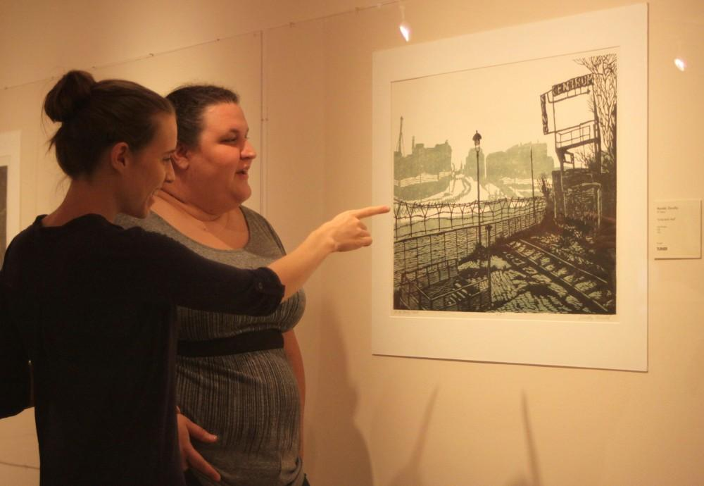 """Norma Loya Graduate students Trinity Stanio and Adria Davis observe  """"At the Berlin Wall"""" by Dorothy Mandel at the Turner Print Museum. The piece was printed using a color woodcut method in 1970."""