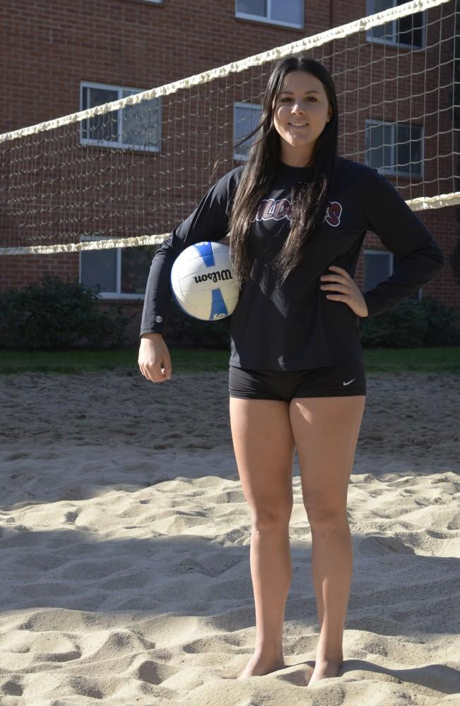 Photograph by Dan Reidel Freshman setter Torey Thompson poses on a beach volleyball court in front of Lassen Hall.