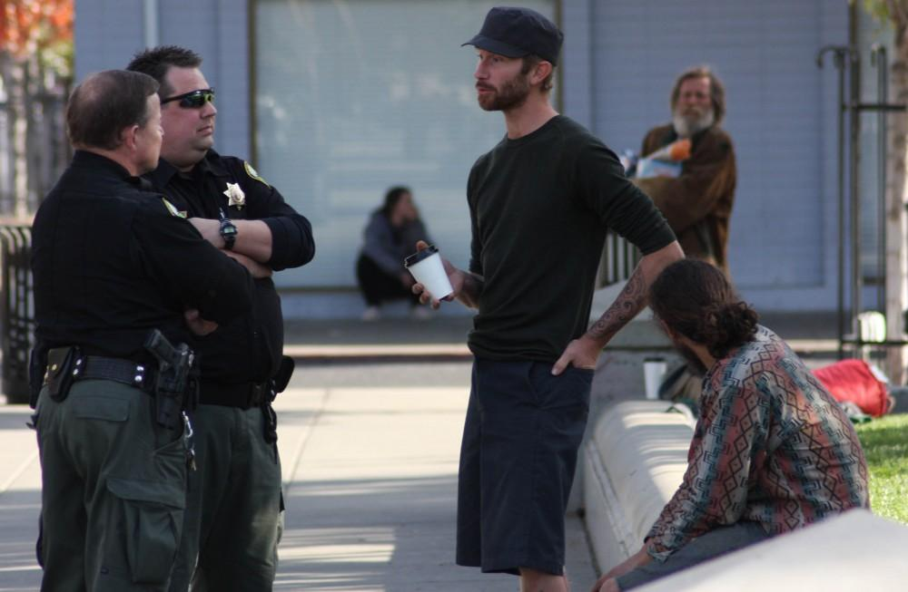 By Shelby Keck Security guards A. Carpenter and B. Stevens talk with Ryan Laine Wednesday, Nov. 6, in the City Plaza the day after the Chico City Council approved the sit-and-lie ordinance.Photo credit: Shelby Keck.
