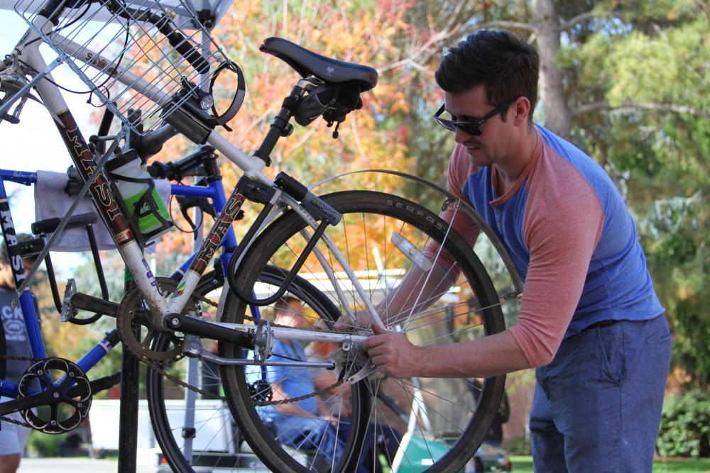 Tanner Lyon fixing a bike at the Associated Students Bike Cart. Photo by Riley Mundia