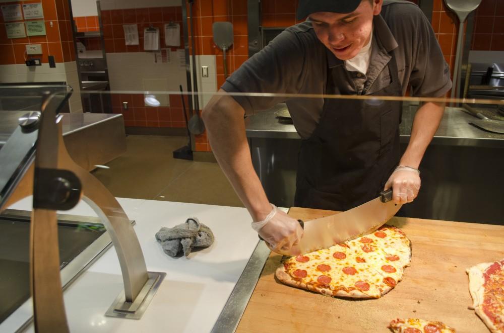 Photograph by Mozes Zarate Vincent Fuentes, senior business major, prepares a pizza at Sutter Dining.