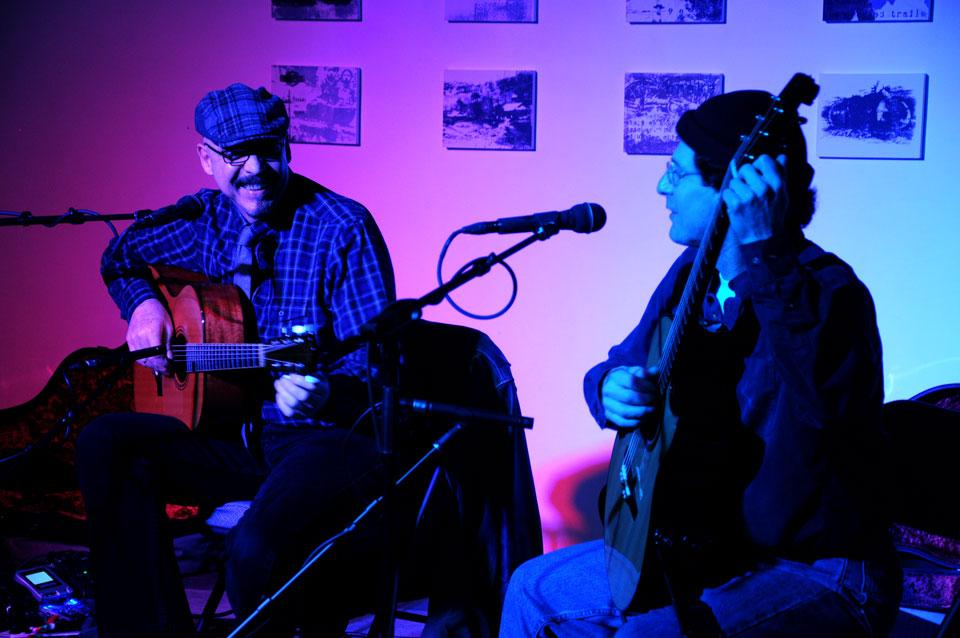 Peter Janson, left, warms up the crowd to their next song by explaining that the only person he could ever play well with is Larry Pattis, musically and in real life. Photo credit: Annie Paige