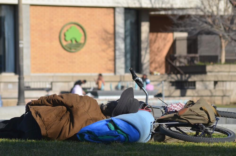 A homeless man sleeps on a grassy area of the downtown plaza facing the city chambers, where many transients often reside.Photo credit: Jamie Stryker
