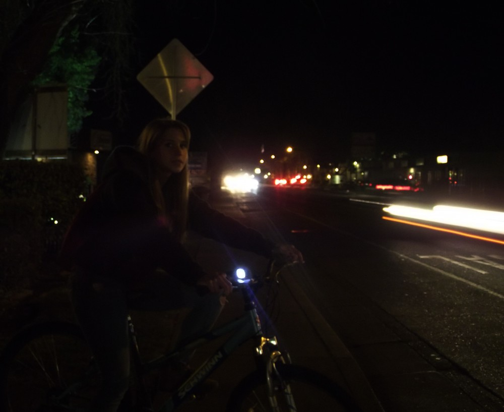 Stephanie Kraker, age 20, a junior hospitality major, rides her bike home at night.Photo credit: Frances Mansour