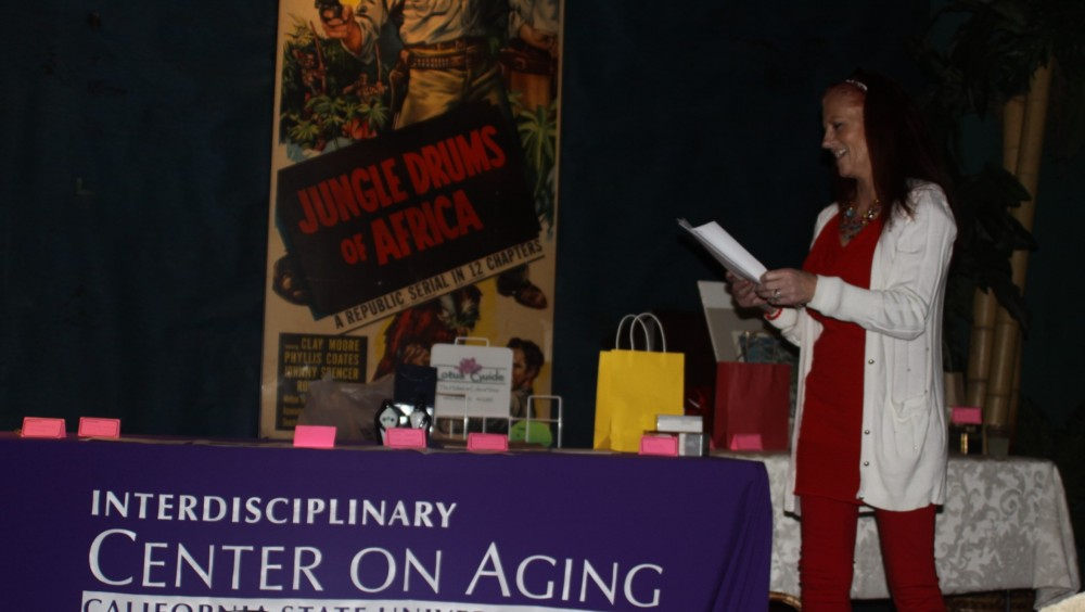 Maggie Zuckerman, a junior social work major, announced the prizes from Saturday's silent auction at the Pageant Theatre.Photo credit: Shayla Ramos