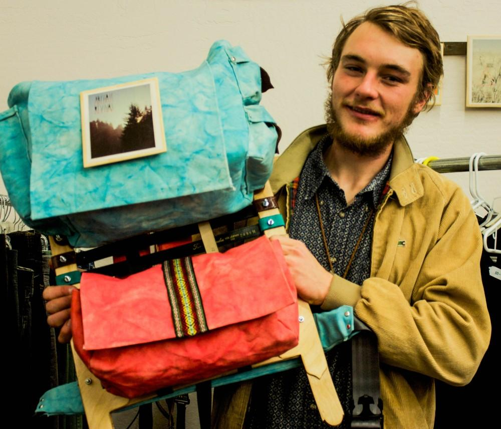 Artist Christian Laney-Clark presents one of his handmade backpacks at the Saturday night reopening of BOHO.Photo credit: Chelsea Jeffers