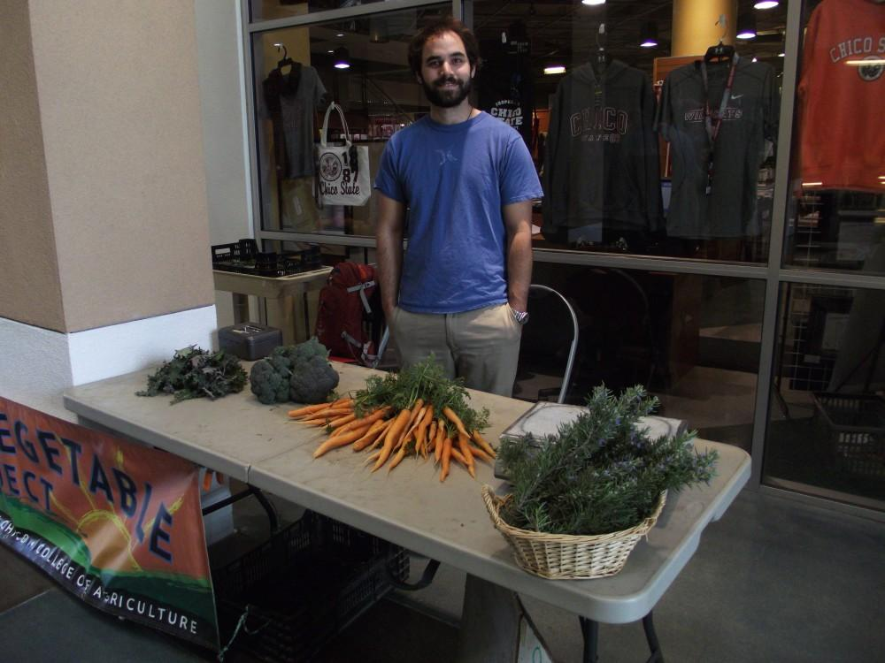 Kyle Riddle, a senior agricultural business major, works the table for the Organic Vegetable Project inside the Bell Memorial Union.Photo credit: Frances Mansour