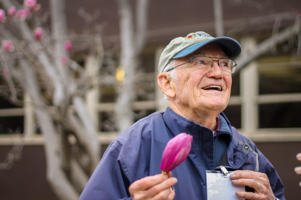 Wes Dempsey, 82, Chico State's arboretum guide, excitedly explains the magnolia flower to the audience.Photo credit: Maisee Lee
