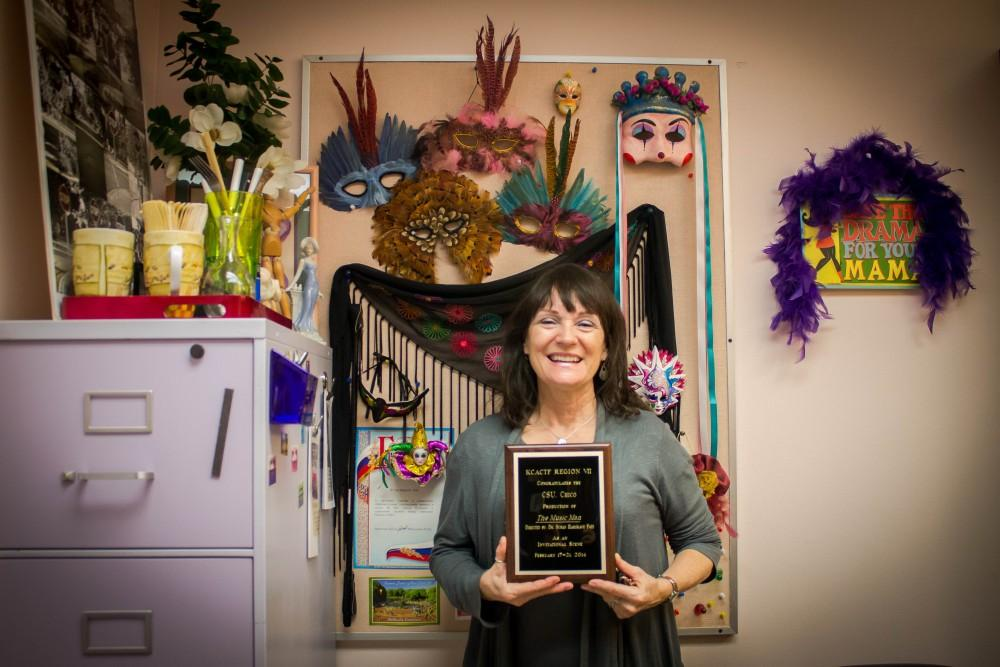 Sue Hargrave Pate, a retiring Chico State Arts Professor, holds up an award while standing behind a wall she calls