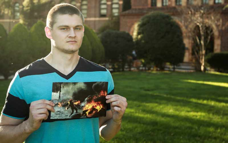 Yaroslav Lazurenko, a Chico State student who moved to Chico from Ukraine eight years ago, holds a photo of rioting in his country. Photo credit: Emily Teague