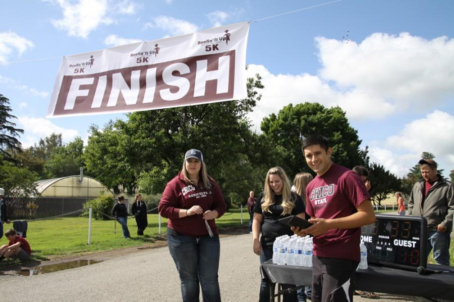 Cain Madrigal, president of the Young Cattlemans Association, keeps track of time for about 60 runners at the Beefin it Up 5K. The event was held at the University Farm and open to the public. Photo credit: Shayla Ramos