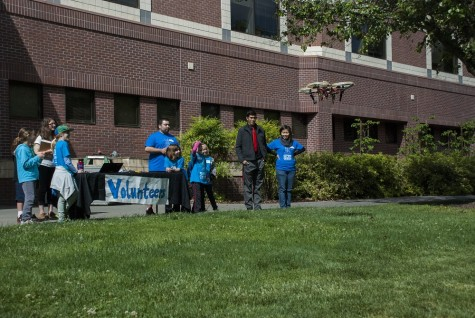 Chico State engineering students fly a miniature helicopter with children participating in Imagineer Day. Photo credit: Alex Boesch