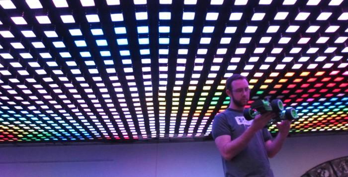 Jordan Layman, co-founder of Idea Fab Labs, examines an RC car under thousands of LED pixels suspended from the ceiling. Photo credit: Emma Wood-Wright