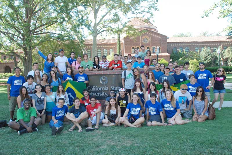 International students in the Brazlus club on campus sit in front of Chico State. The club is for students who are interested in the Brazilian culture and Portuguese language. Photo courtesy of Cem Ustundag.