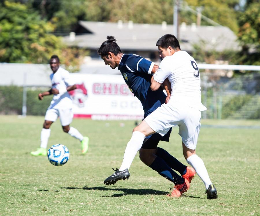 Octavio Murillo grapples with the opposition as both players go for the ball. Photo credit: Emily Teague
