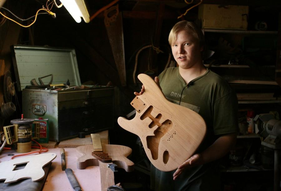 Evan Kelsay, 22, presents one of the unique pieces he's created at his workshop in Paradise. Kelsay is the owner and operator of Apocalypse Guitars, a custom-guitar building and repairing service. Photo credit: John Domogma