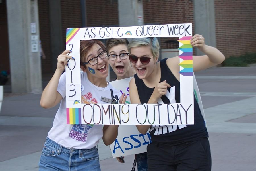 Emilee Hunt, Rachel Ward and Alex Dooley pose with a National Coming Out Day frame. Photo credit: Emily Conroy