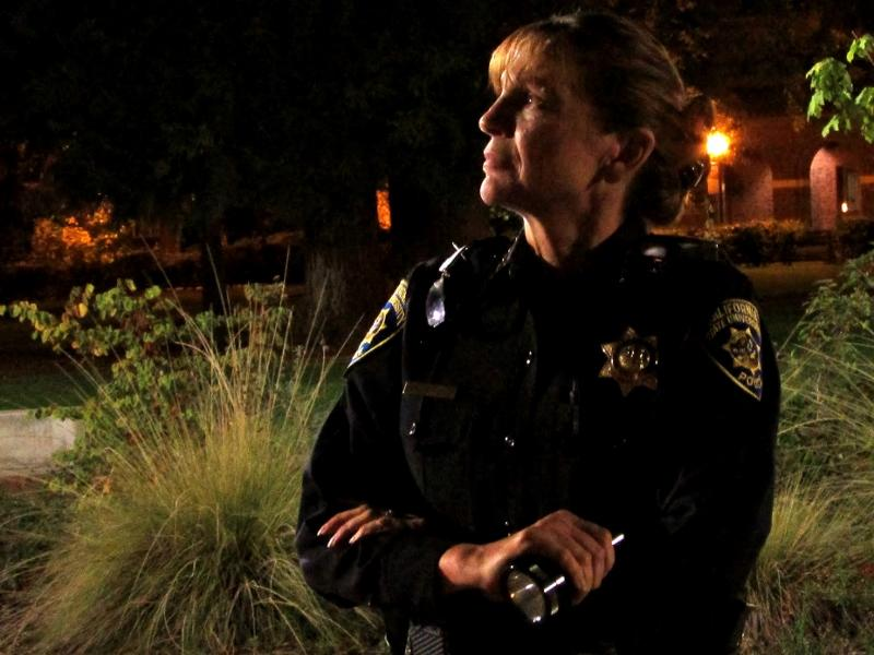 Police Chief Robyn Hearne examines the outside of the Performing Arts Center for broken light fixtures during the 10th annual Moonlight Safety Walk 8 p.m. Thursday. Hearne, who has participated in the walk every year, led the group examining the campus core. Photo credit: Ashiah Scharaga