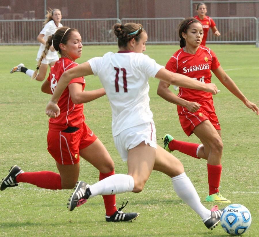 Wildcat Midfielder, Emily Shleppey, makes a strong clearance in front of two attacking Warriors Sunday, September 21, 2014 at Wildcat Stadium. Photo credit: John Domogma