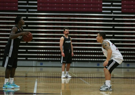 Chico State basketball player Jalen McFerren, left, sets up the offense with guard Mike Rosaroso, right, playing defense. Photo credit: John Domogma