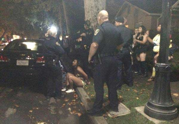 A woman handcuffed for public intoxication, Oct. 31. Photo credit: Lindsay Pincus