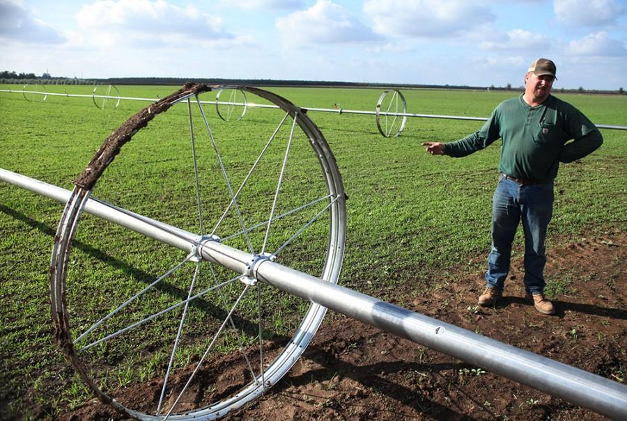 Farm staff member Kevin Renker explains how newly-installed waterlines irrigate the field at the University Farm. Photo credit: John Domogma