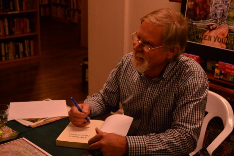 Paradise author Ken Young signs a copy of his first novel for a fan at the book's presentation Tuesday at Lyon Books. Photo credit: Veronica Hodur