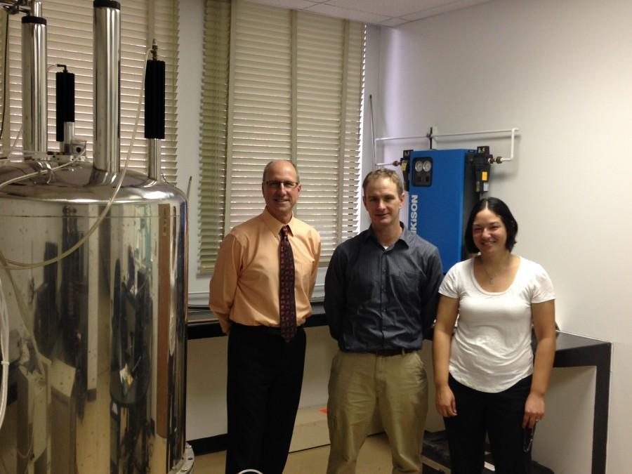 Randy Miller, left, chemistry and biochemistry department chair, Dan Edwards, middle, and Carolyn Edwards, both chemistry and biochemistry professors, stand next to the department's nuclear magnetic resonance spectroscopy. Photo credit: Amanda Rhine