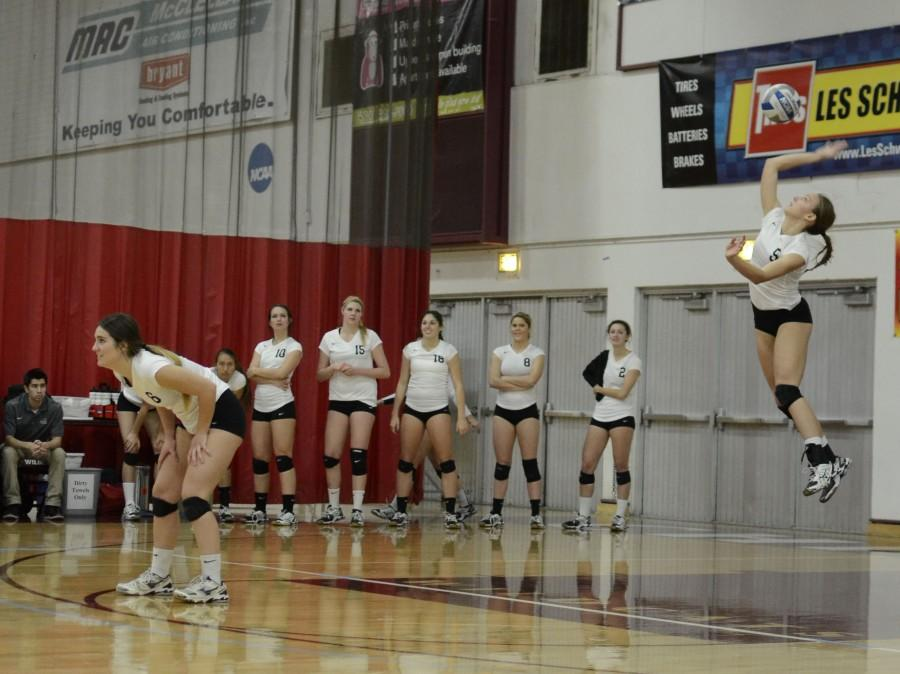 Senior middle hitter Lindsay Quigley takes flight and serves the ball in a match against Humboldt State in November 2013. Orion file photo.