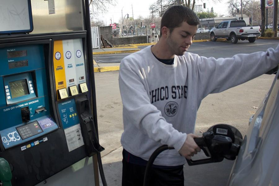 Chico State senior Michael Belcher fills up his tank at a gas station on Walnut Street. OPEC has not cut back on crude oil production yet so prices have remained low. Photo credit: Gustavo Ornelas