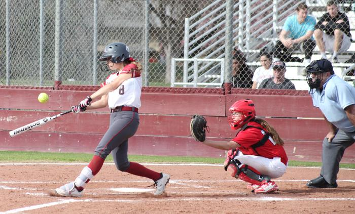 Junior Wildcat Amanda Cordeiro hits the ball towards left field Feb. 12, during a match against University of Hawaii-Hilo. Photo credit: John Domogma