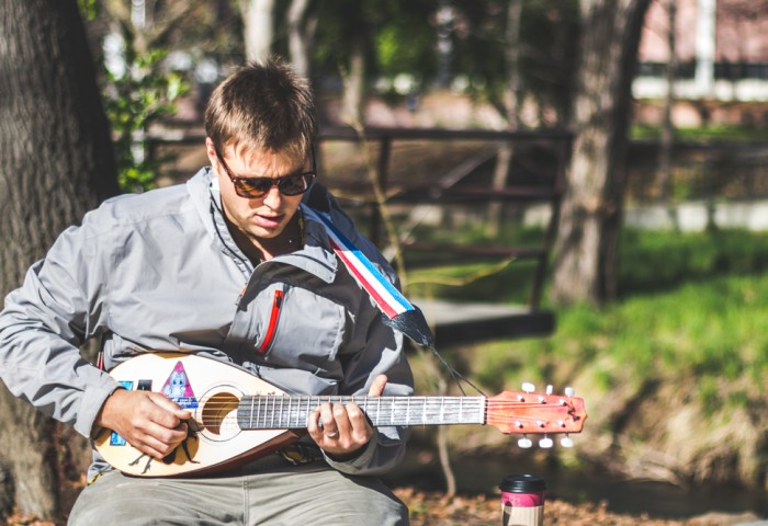 During a break between classes Chico State student Ira Salamon takes the opportunity to play a small travel guitar outside Creekside Coffee. Photo credit: Trevor Ryan