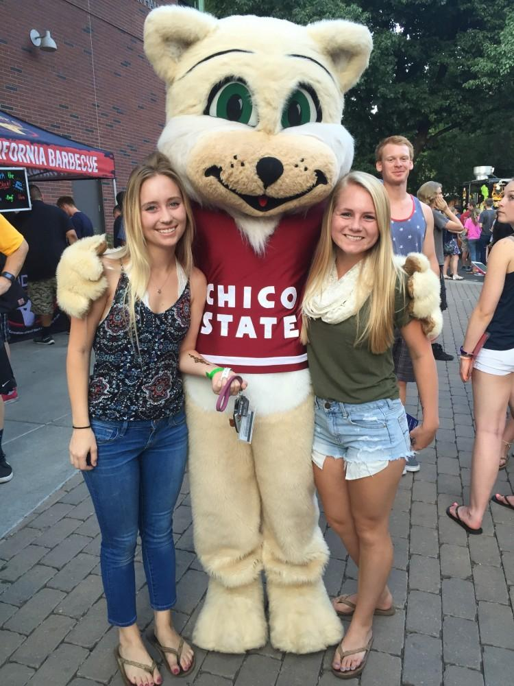 Resident advisers Sara Tengelsen and Emmeline Hurley pose with Willie Wildcat at Rock the Block. Photo credit: Carly Plemons