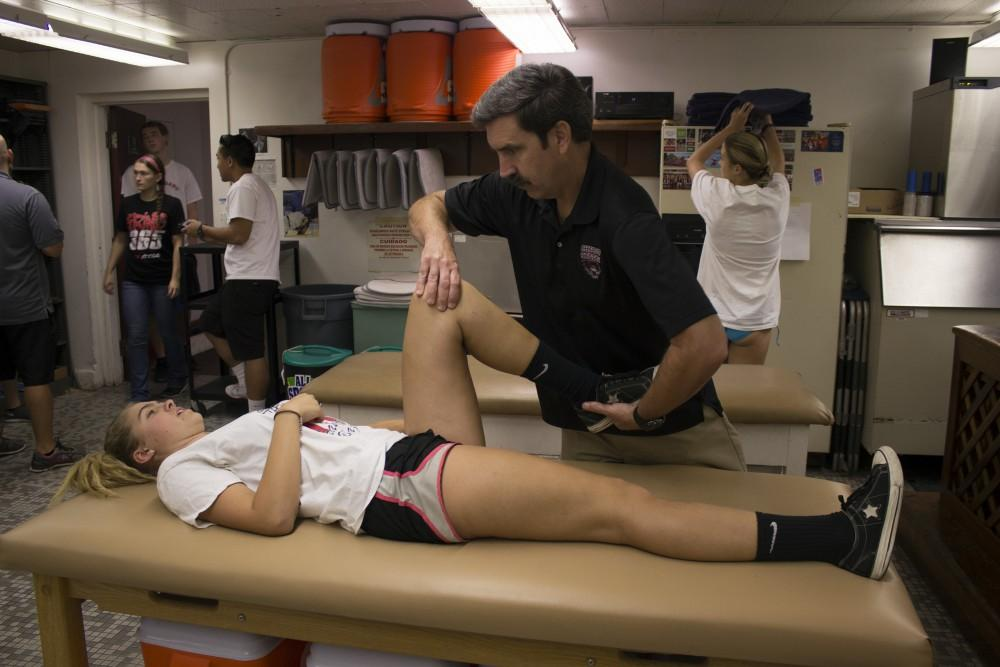 Chico State's head athletic trainer, Scott Barker, feels for abnormalities in first-year softball player Megan Bowley's knee. Photo credit: Christine Zuniga