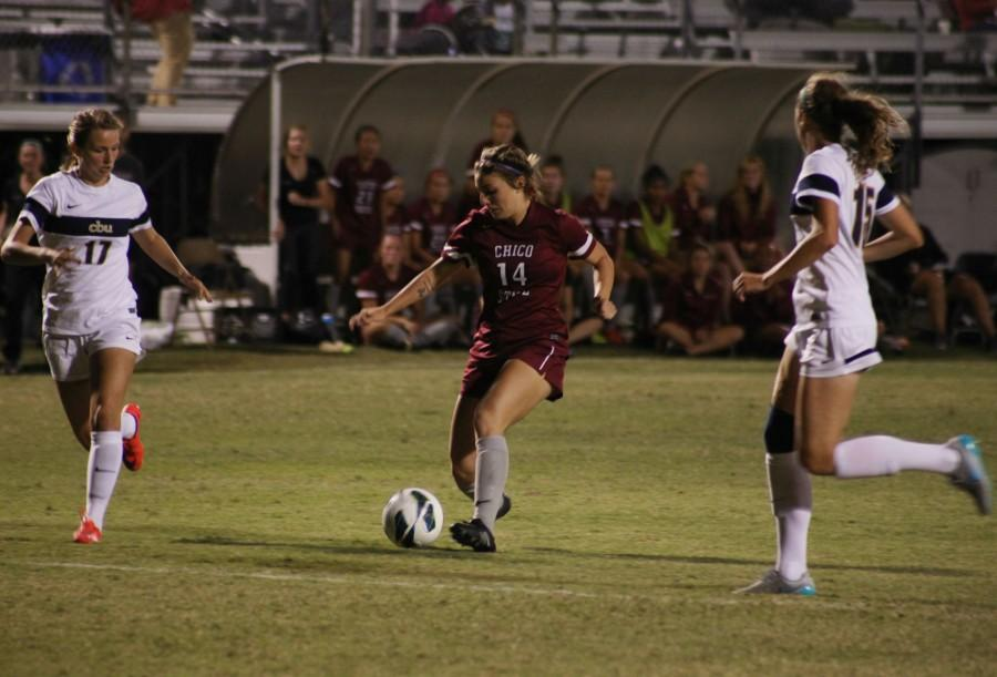 Carlie Reader, first-year women's soccer player,  passes the ball up the field. Photo credit: John Domogma
