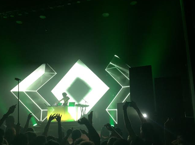 Madeon pumps up the crowd on Saturday, Sept. 19 in an eery green light shroud. Photo credit: Dana Muensterman