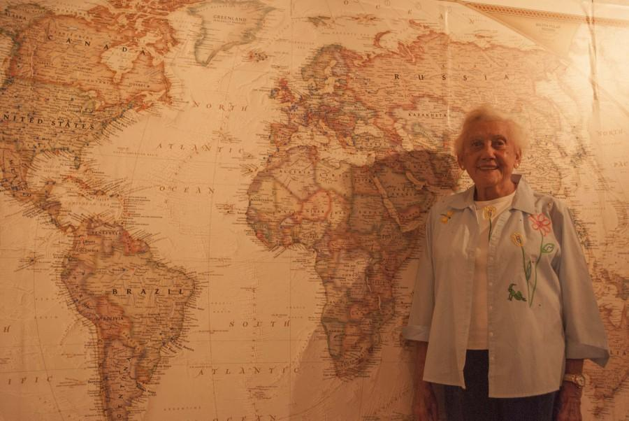 Valene Smith in front of the world map in her anthropology museum sharing the many stories of her travels around the world. Photo credit: Sam Barker