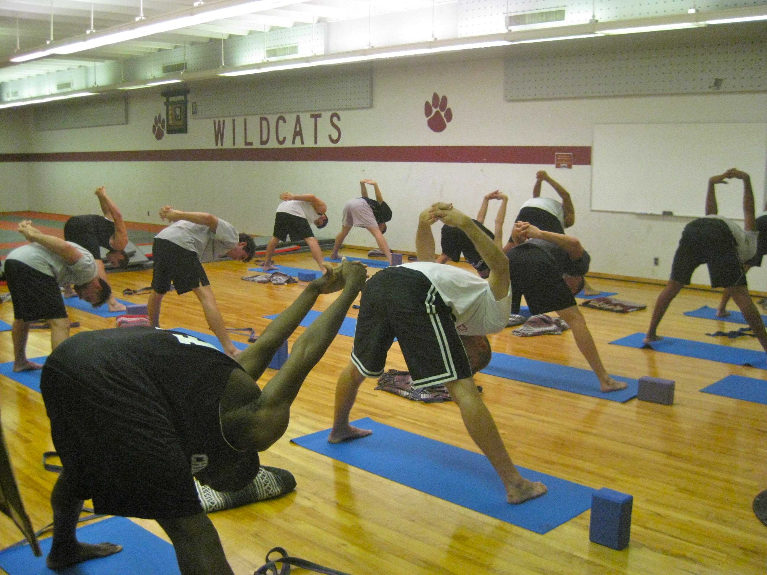 The 2014 men's basketball team practices the uttanasana pose during a yoga session. Photo courtesy of Rex Stromness.