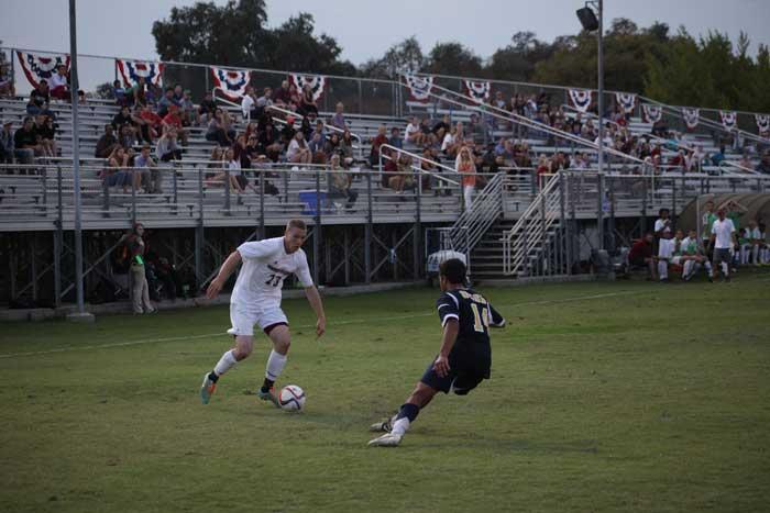Senior forward Matt Hurlow dribbles by a defender. Photo credit: John Domogma