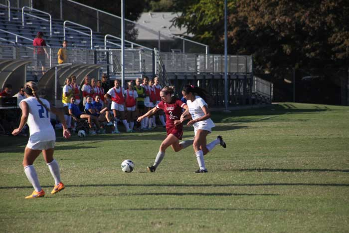 Senior+defender+Cassi+Scroggins+fights+off+her+opponent+for+possession+of+the+ball.+Photo+credit%3A+John+Domogma