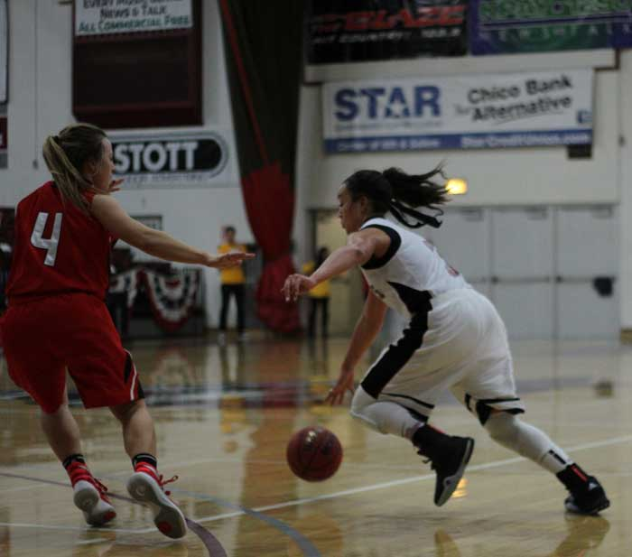 Sophomore+Whitney+Branham+dribbles+around+her+opponent+in+a+game+against+Cal+State+Stanislaus.+Photo+credit%3A+Jordan+Olesen