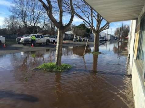 Water pools in front of businesses as Cal Water crews try to reverse flooding. Photo credit: Michael Catelli