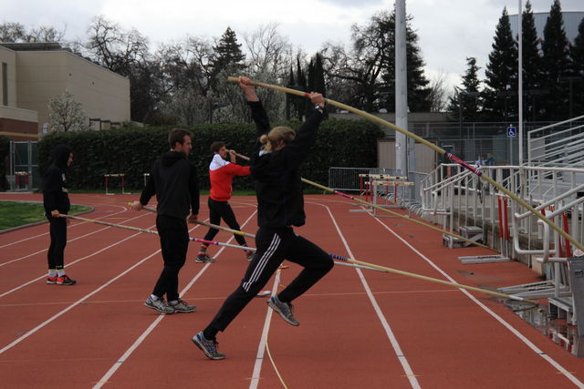 Track and field pole vaulters warm up before practice on a cold day. Photo credit: Cam Lesslie