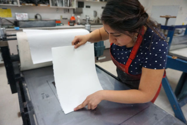 Gonzalez+carefully+places+her+paper+onto+the+printing+press+to+get+her+piece+directly+onto+the+center+of+the+paper.