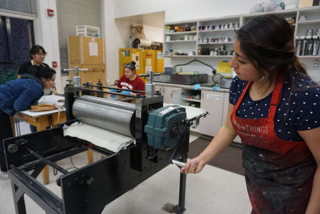Gonzalez+is+seen+running+her+copper+plate+through+the+printing+press.