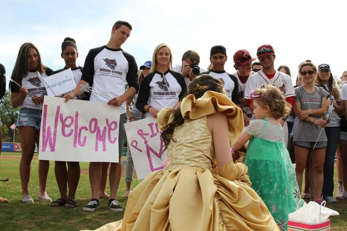 Four-year-old Davan Jones receives her gift as student athletes look on. Photo credit: Jordan Olesen