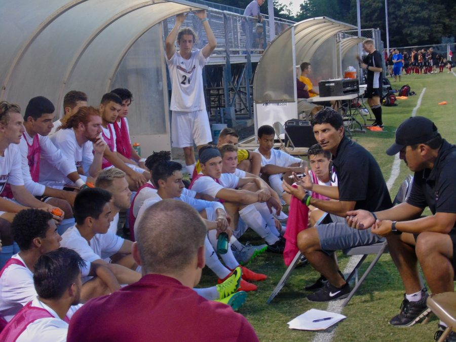 The Chico State men's soccer team gathers around their coach at half time. Photo credit: Royal T Lee-Castine