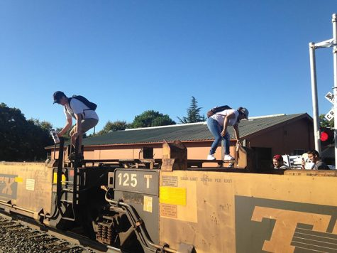 Students climbing over stalled train to get to campus. Photo credit: George Johnston