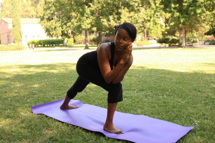 Junior Dejohnette Williams does yoga in the small park next to Glenn Hall Photo credit: Jovanna Garcia